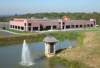 exterior of manicured commercial property grounds, fountain and pond
